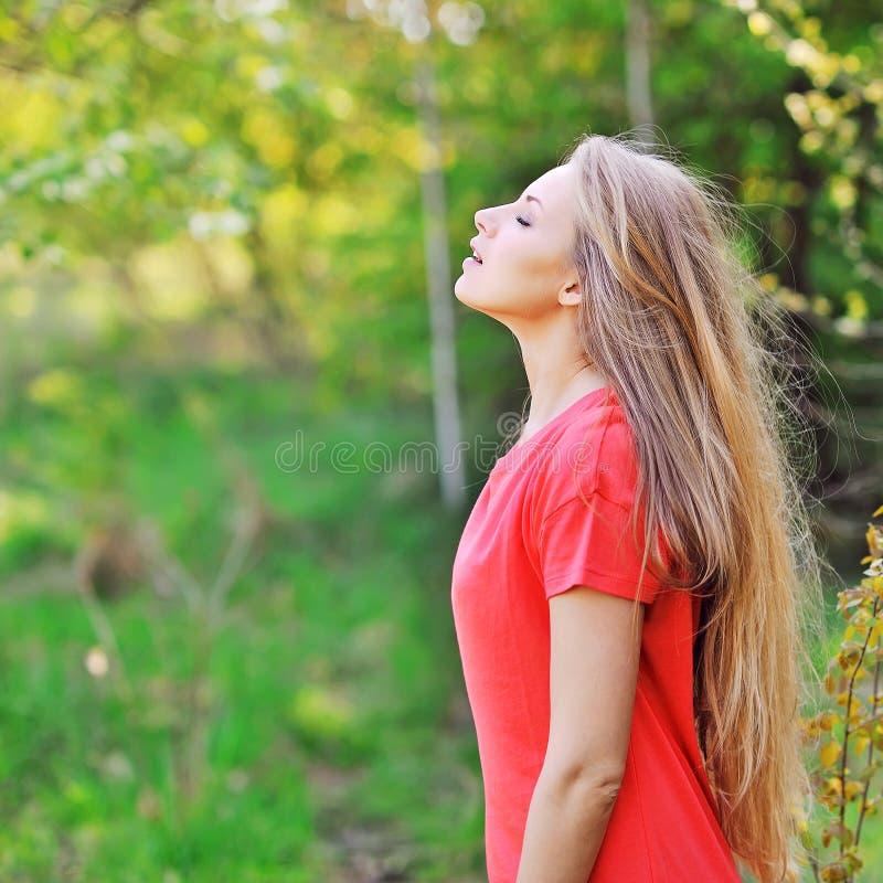 Молодая счастливая усмехаясь женщина делая глубокий вдох стоковое изображение rf