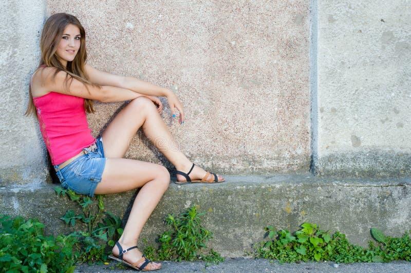Молодая счастливая усмехаясь & смотря женщина камеры сидя на сером copyspace предпосылки стены стоковые фото