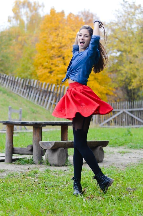 Молодая счастливая юбка женщины вкратце красная закручивая вокруг стоковые фото