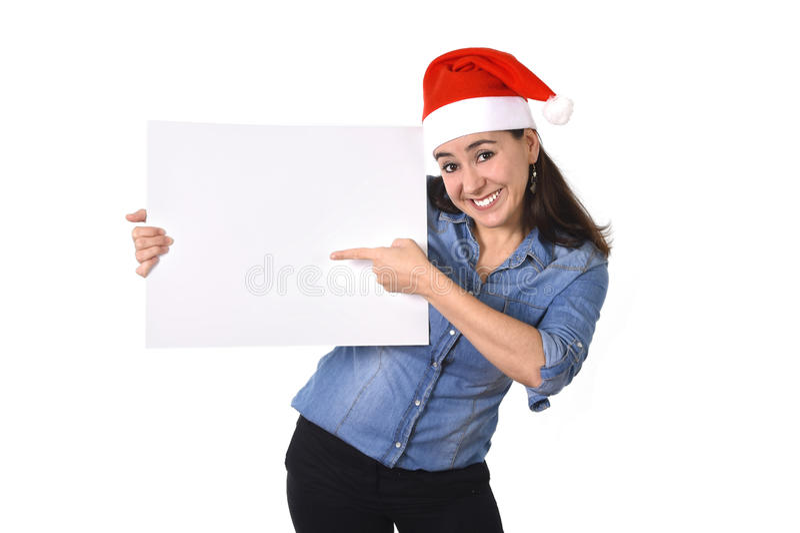 Молодая сладостная латинская женщина в шляпе рождества Санты указывая пустая афиша стоковая фотография