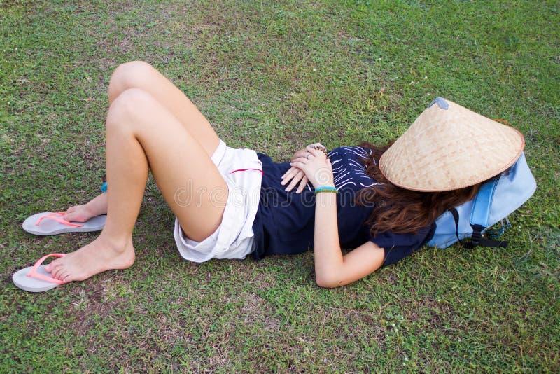 Молодая туристская дама лежа на спать зеленой травы стоковая фотография rf