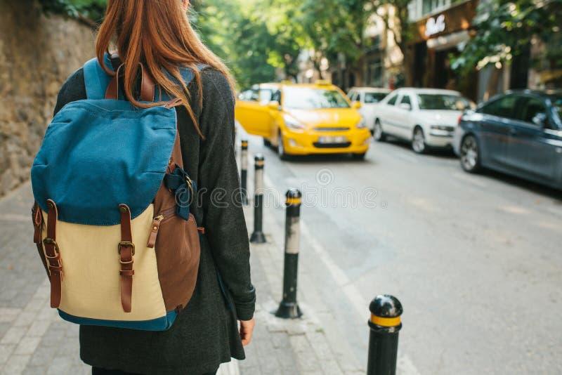 Молодая туристская девушка с рюкзаком в большом городе ждет такси Путешествие Sightseeing Путешествия стоковое изображение