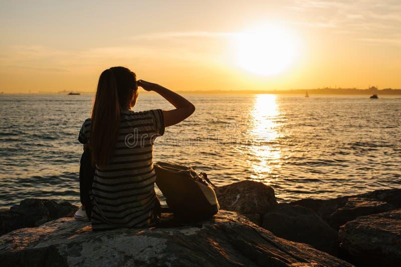 Молодая туристская девушка с рюкзаком сидит на утесах рядом с морем на заходе солнца и смотрит в расстояние остальные стоковые изображения rf