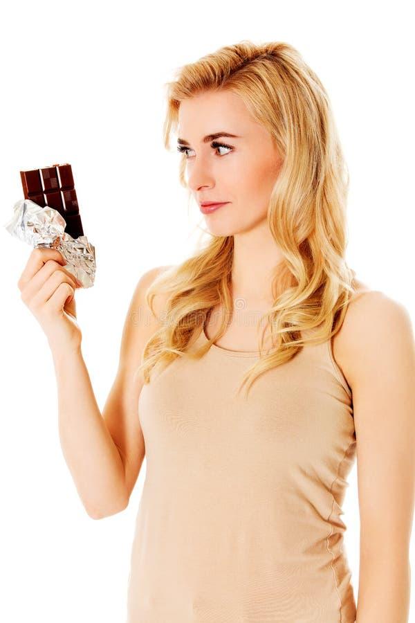 Молодая унылая женщина с шоколадом в руке стоковое изображение rf