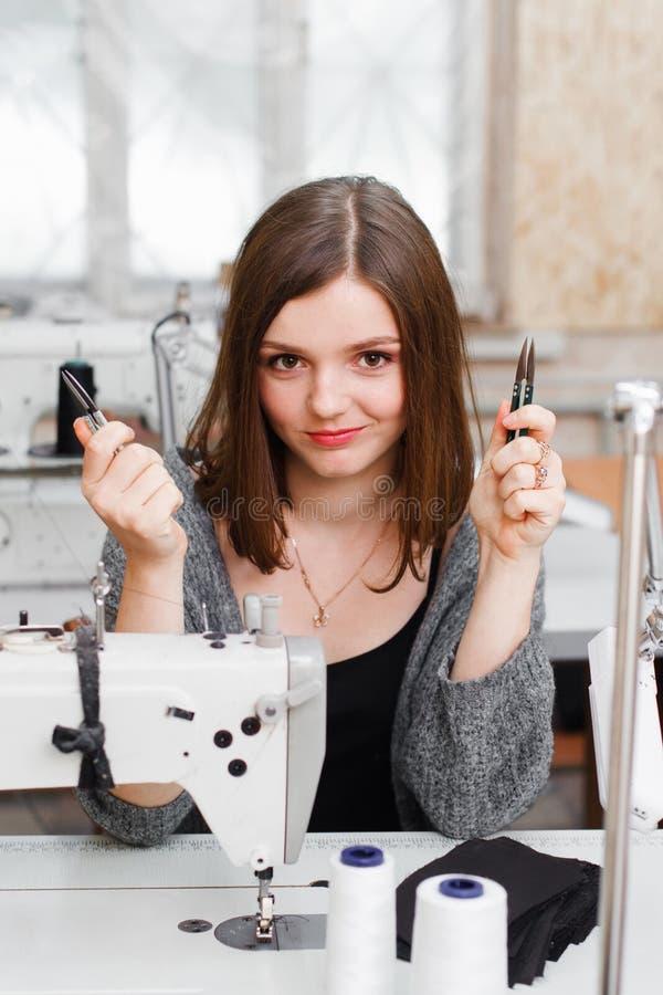 Молодая усмехаясь белошвейка представляя с ножницами стоковые фото