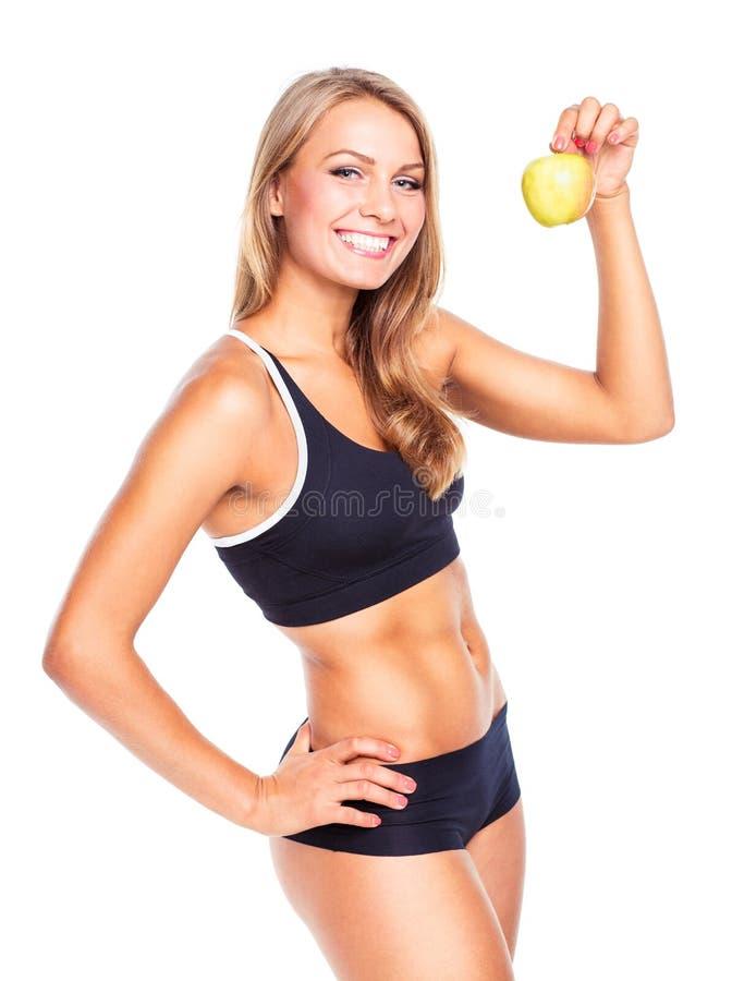 Молодая усмехаясь девушка держа зеленое яблоко в руке стоковые изображения rf