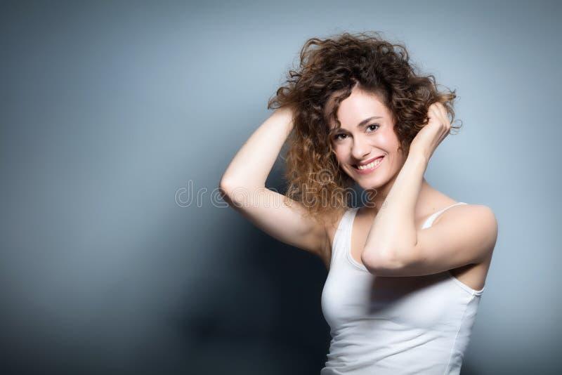 Молодая усмехаясь женщина держа ее вьющиеся волосы вверх стоковое фото rf