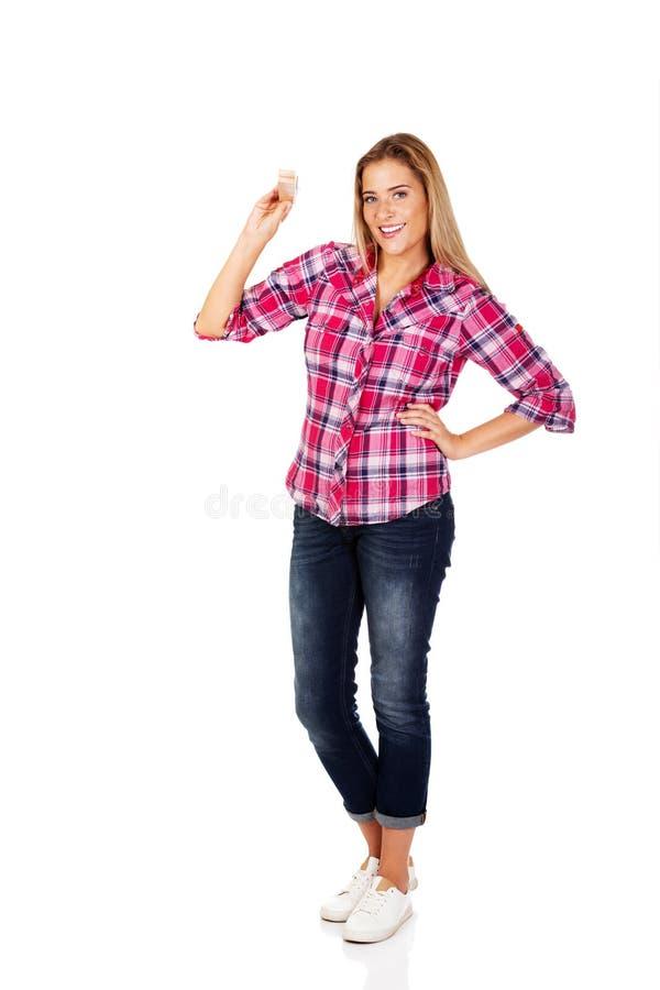 Молодая усмехаясь женщина держа огромный штырь ткани стоковая фотография