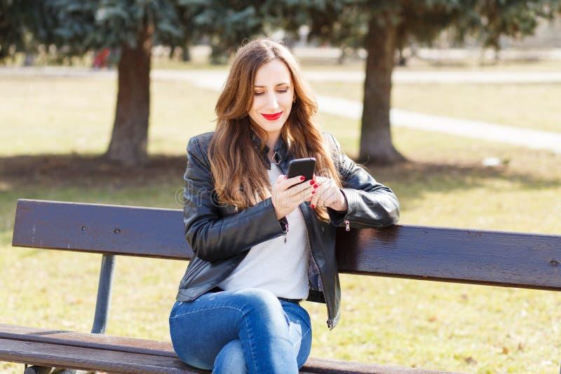 Молодая усмехаясь женщина используя smartphone в парке стоковые фотографии rf