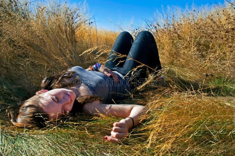 Молодая усмехаясь женщина кладя вниз в длинное желтое поле травы с предпосылкой голубого неба стоковые изображения rf