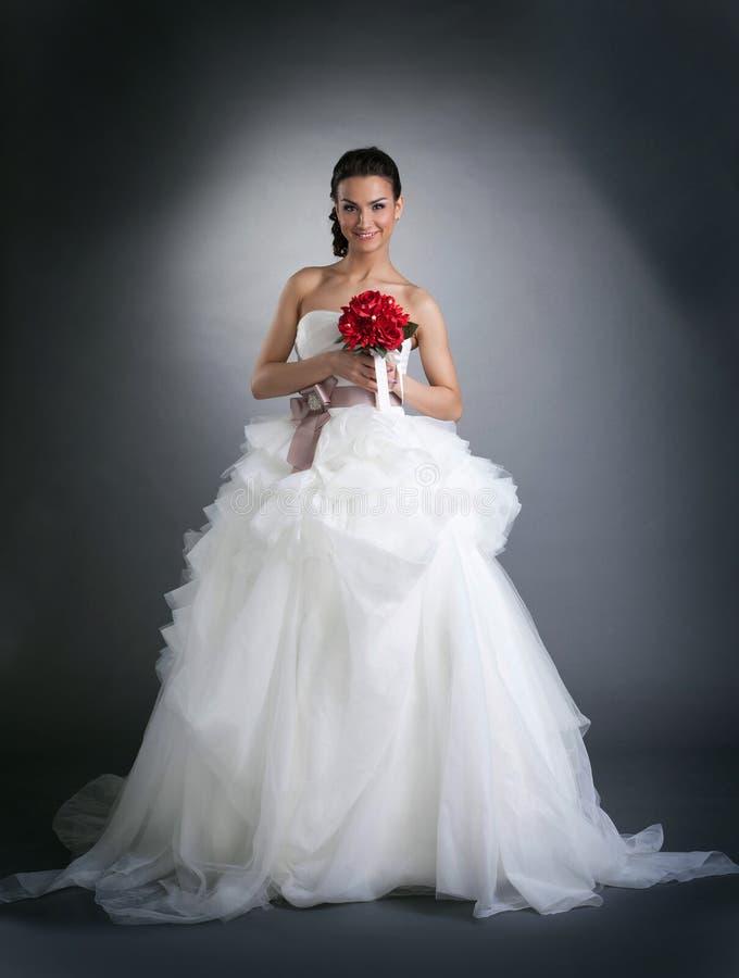 Молодая усмехаясь женщина представляя в платье свадьбы стоковые фотографии rf