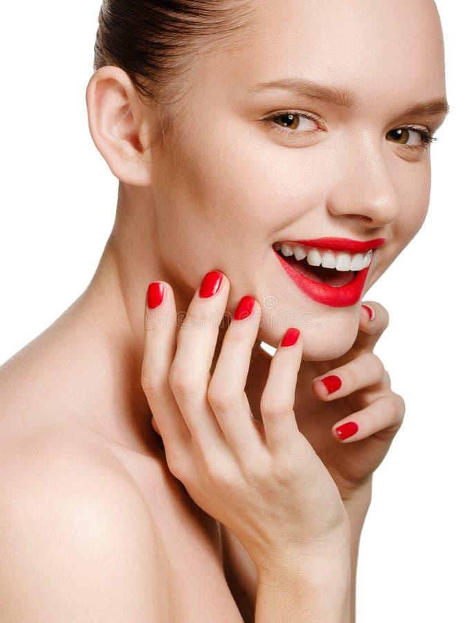 Молодая усмехаясь женщина при красные губы и красные ногти, касаясь ее fa стоковые изображения