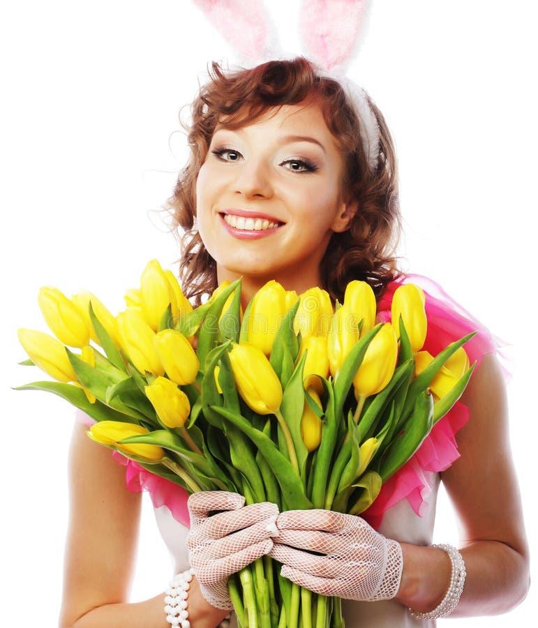 Молодая усмехаясь женщина с желтыми тюльпанами стоковая фотография