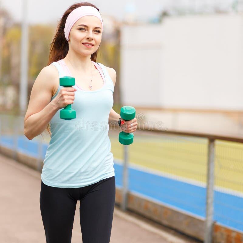 Молодая усмехаясь женщина jogging с гантелями стоковое изображение