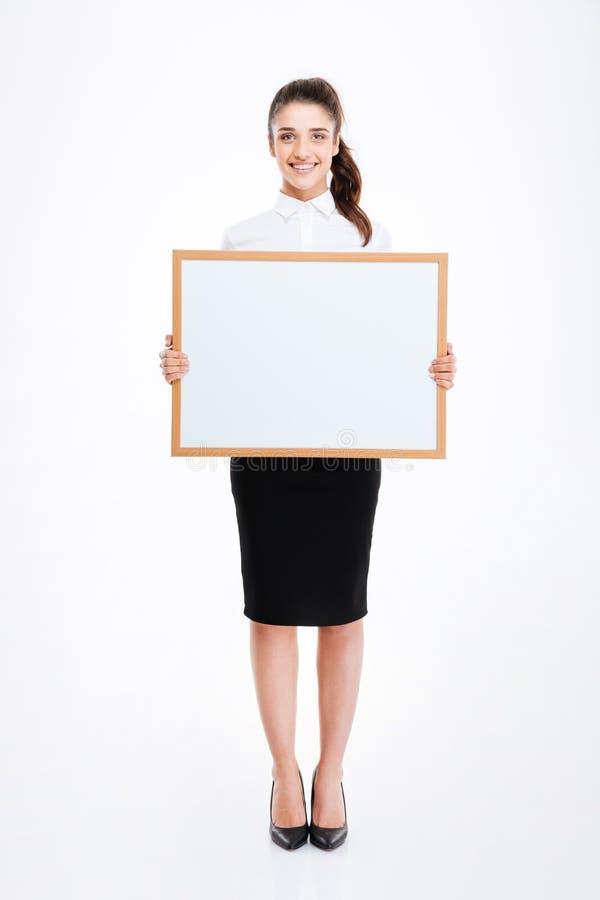 Молодая усмехаясь коммерсантка держа пустую доску стоковое изображение rf