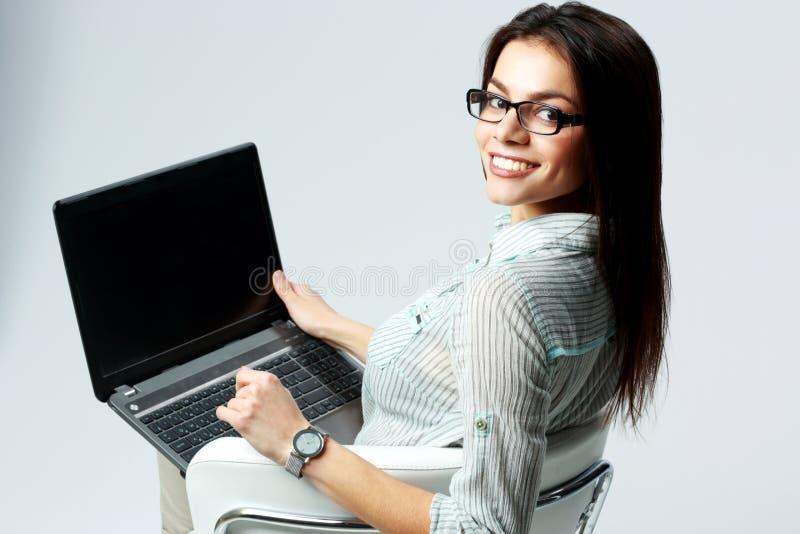 Молодая усмехаясь коммерсантка используя компьтер-книжку стоковая фотография