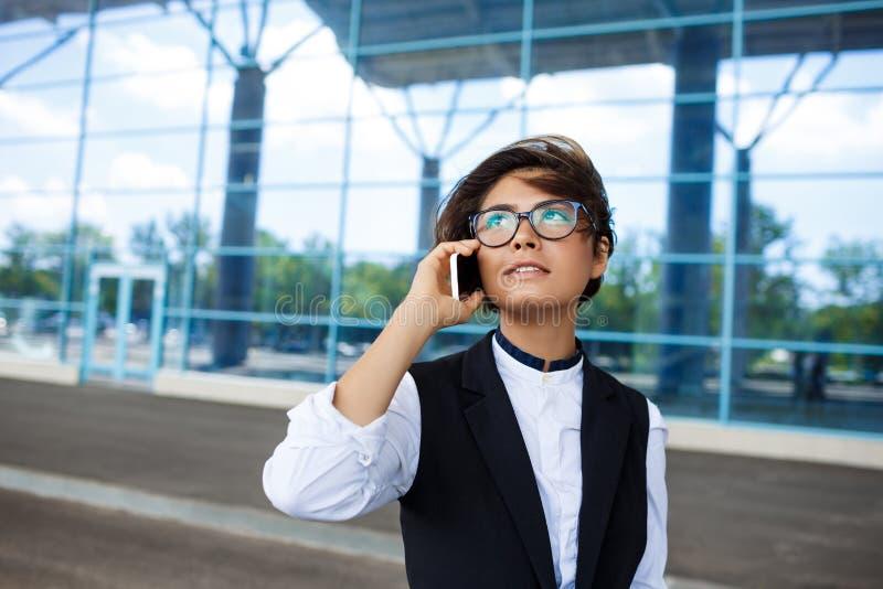 Молодая успешная коммерсантка говоря на телефоне, стоя близко бизнес-центре стоковые фотографии rf