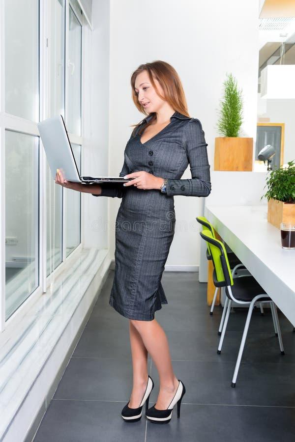 Молодая успешная коммерсантка при портативный компьютер стоя около окна таблетка компьютера используя женщину Бизнес стоковое изображение