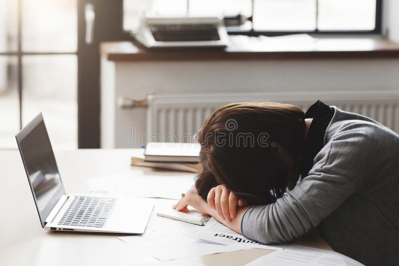 Молодая утомленная женщина спать на столе офиса стоковая фотография