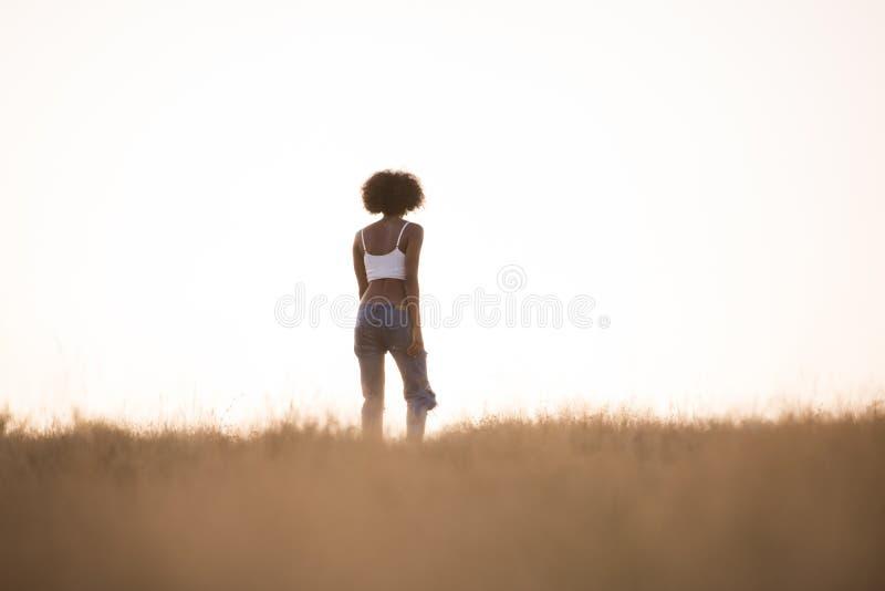 Молодая черная девушка танцует outdoors в луге стоковое фото