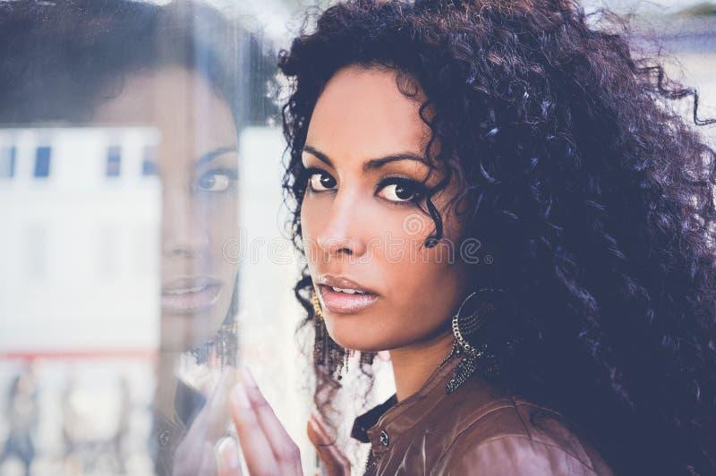 Молодая чернокожая женщина, афро стиль причёсок, в городской предпосылке стоковое изображение rf