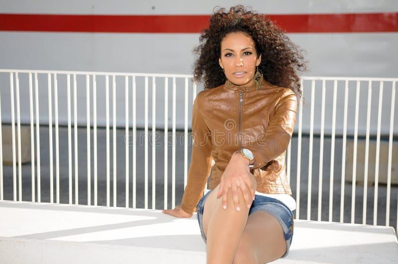 Молодая чернокожая женщина, афро стиль причёсок, в городской предпосылке стоковые фотографии rf