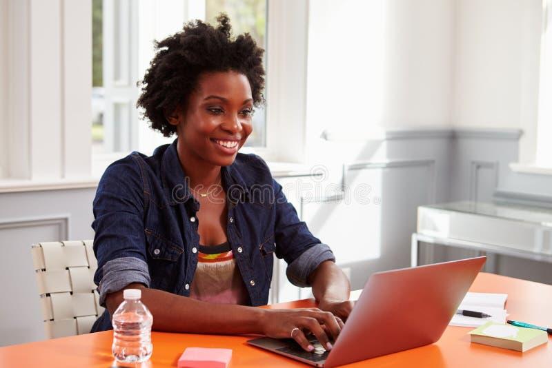 Молодая чернокожая женщина используя портативный компьютер на столе, конец-вверх стоковое изображение