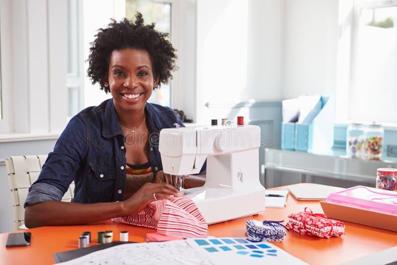 Молодая чернокожая женщина используя швейную машину смотря к камере стоковое изображение rf