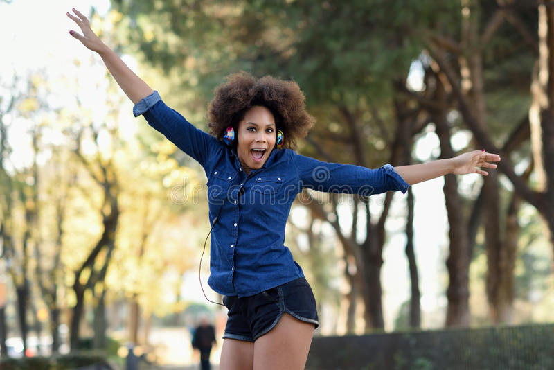 Молодая чернокожая женщина при афро стиль причёсок скача в городское backgroun стоковое изображение