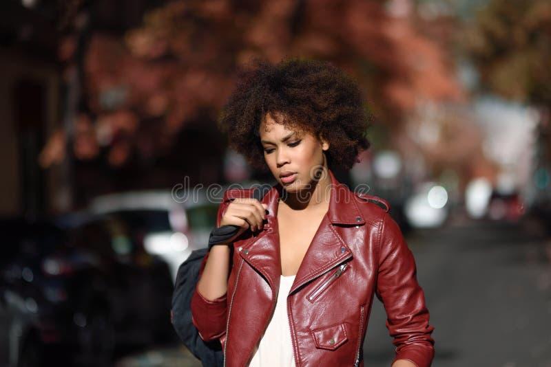 Молодая чернокожая женщина при афро стиль причёсок стоя в городском backgrou стоковые фото