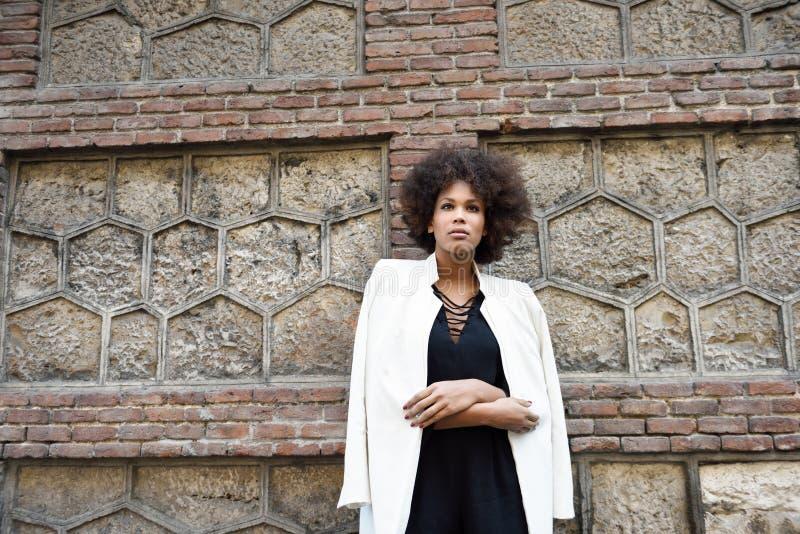 Молодая чернокожая женщина при афро стиль причёсок стоя в городском backgrou стоковое изображение