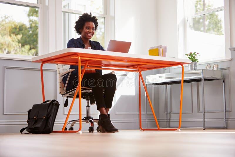 Молодая чернокожая женщина сидя на столе используя портативный компьютер стоковое изображение rf