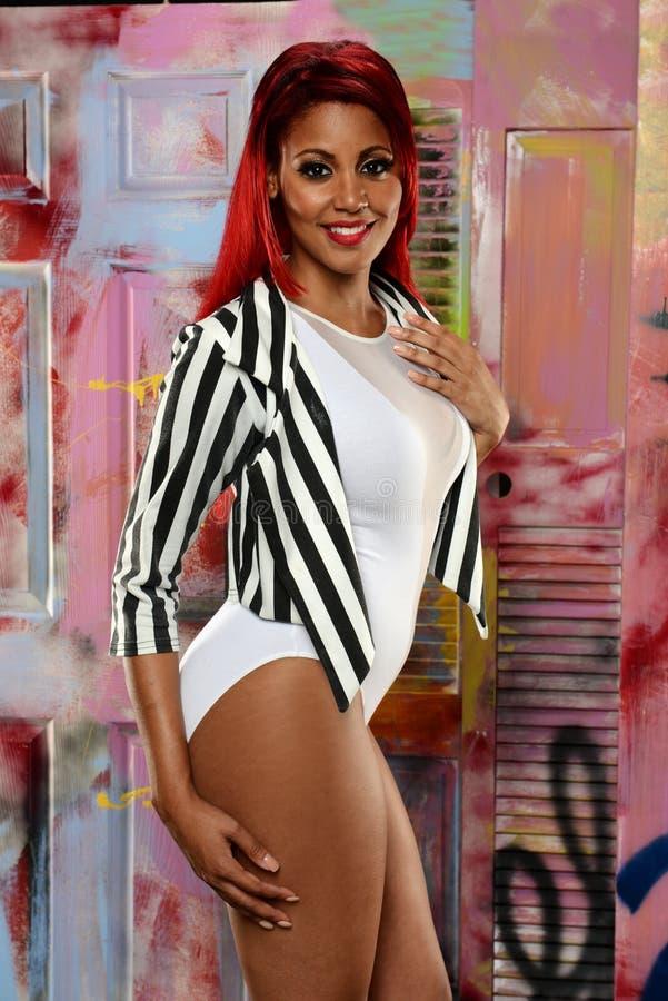 Молодая чернокожая женщина с красными волосами стоковое фото