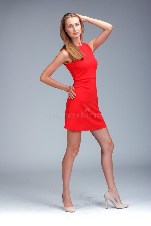 Молодая шикарная кавказская блондинка в красный представлять платья стоковое изображение rf