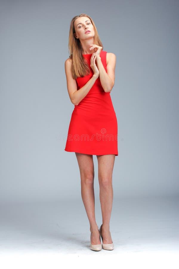 Молодая шикарная кавказская блондинка в красный представлять платья стоковое фото
