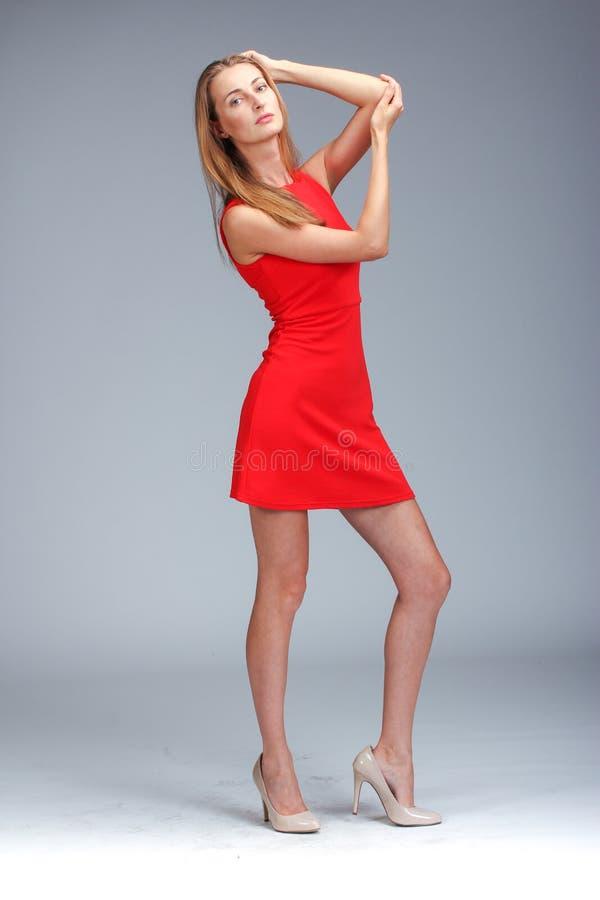 Молодая шикарная кавказская блондинка в красный представлять платья стоковые фото
