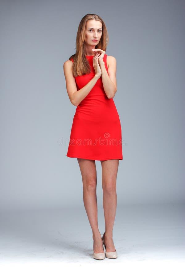 Молодая шикарная кавказская блондинка в красный представлять платья стоковое фото rf