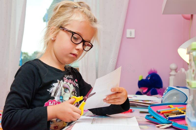 Молодая школьница делая домашнюю работу стоковое изображение