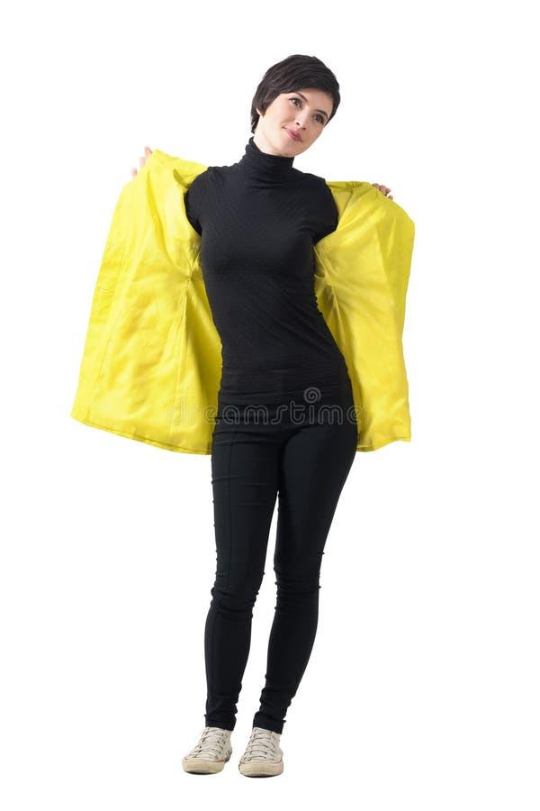 Молодая элегантная женщина в черных одеждах принимая желтое пальто дождя стоковые фото