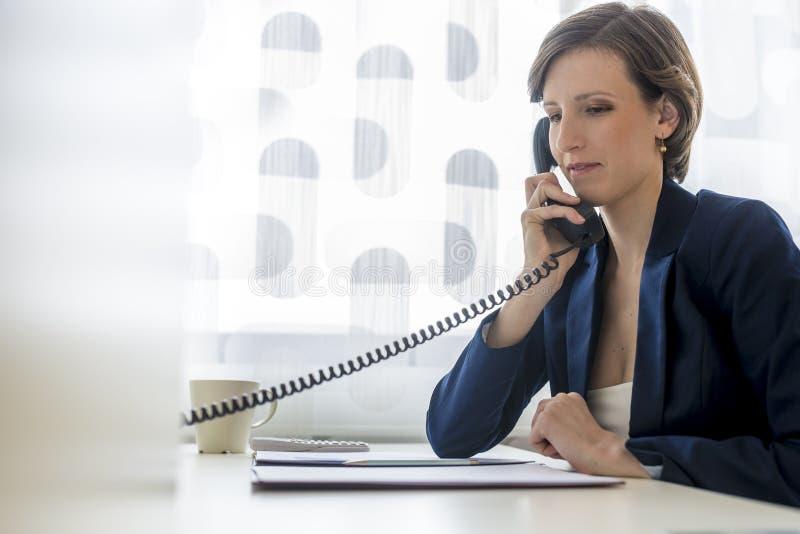 Молодая элегантная коммерсантка сидя на ее столе офиса делая a стоковая фотография rf