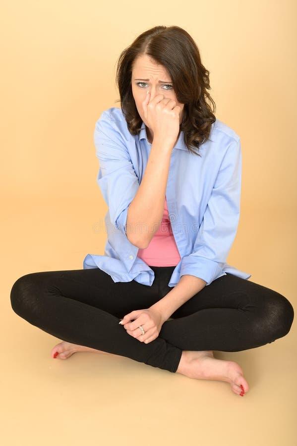 Молодая disgusted несчастная женщина держа нос должный к плохому запаху стоковая фотография
