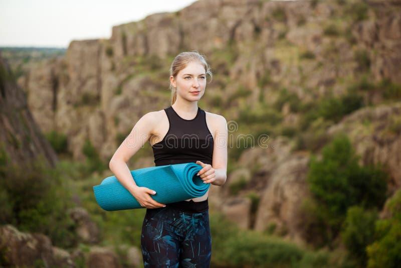 Молодая sportive девушка держа yogamat, стоя на утесе в каньоне стоковые фото