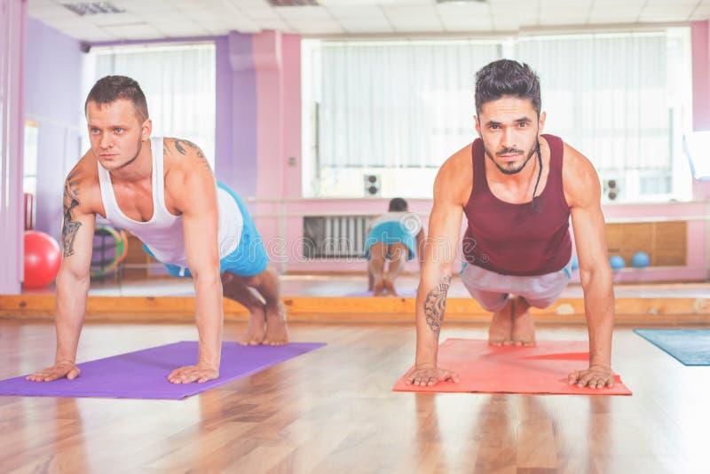 2 молодого человека делая pushups крытые стоковые фото
