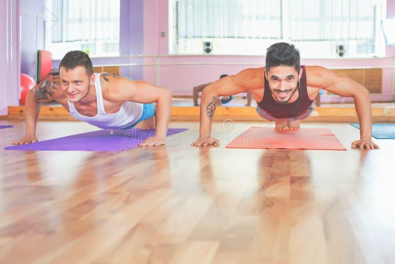 2 молодого человека делая pushups крытые стоковые фотографии rf