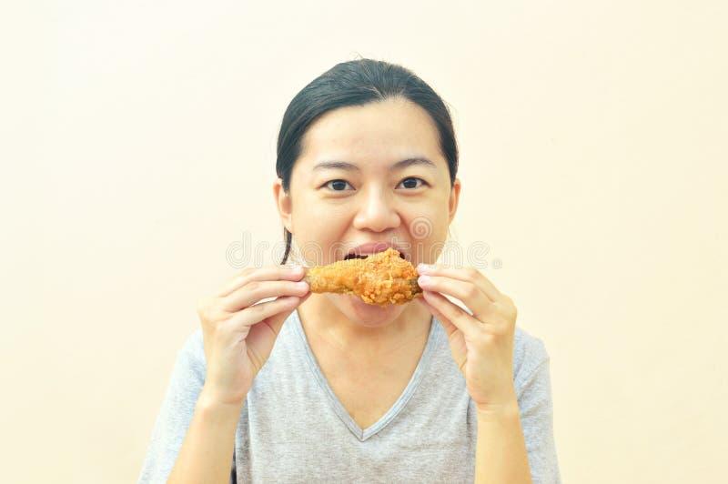 Молодое азиатское удерживание женщины и еда цыпленка фраев стоковое изображение rf