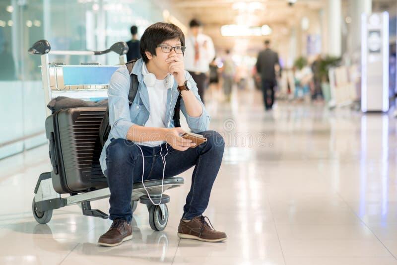 Молодое азиатское чувство человека вымотанное в крупный аэропорт стоковое изображение rf
