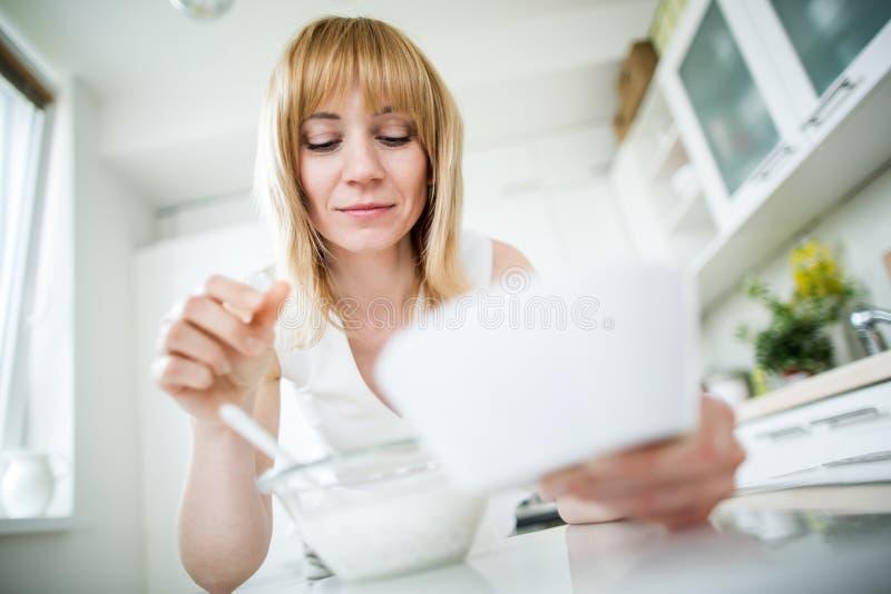 Молодое белокурое muesli еды женщины в кухне стоковые фото