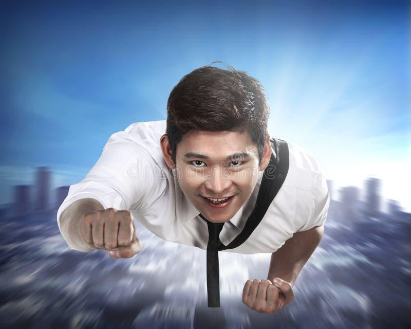 Молодое летание бизнесмена через небо стоковое фото