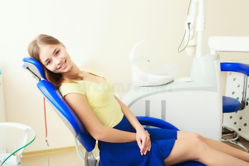 Молодое женское усаживание в офисе дантиста стоковые фото