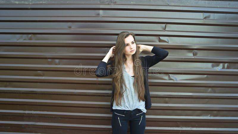 Молодое длинное с волосами брюнет представляя против коричневой загородки металла, тонизированного изображения стоковые фотографии rf
